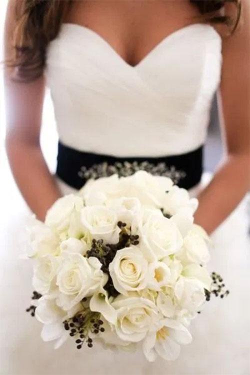 Ramo de novia en blanco y negro con traje de novia blanco y fajín de color negro con pedrería