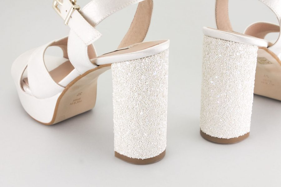 Comfortable bridal shoes with a platform and a wide heel. Wedding sandals tied and fastened
